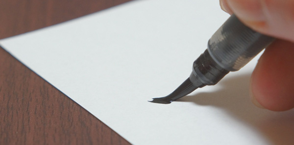 筆ペンで名前を書く